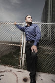 Image of a handsome young businessman posing by a fence — Foto Stock