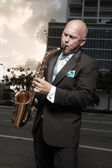 Handsome bald man playing a saxophone — Stock Photo