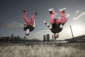 Image of two men performing a midair flip — Stock Photo