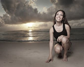 Woman kneeling on the sand — Stock fotografie