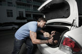 Man stuffing a dead body in his car trunk — Stock Photo