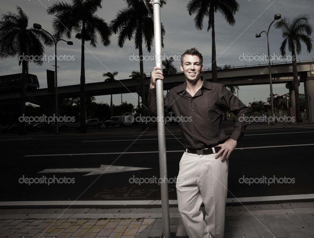 Handsome man leaning on a metal pole — Stock Photo #2586736
