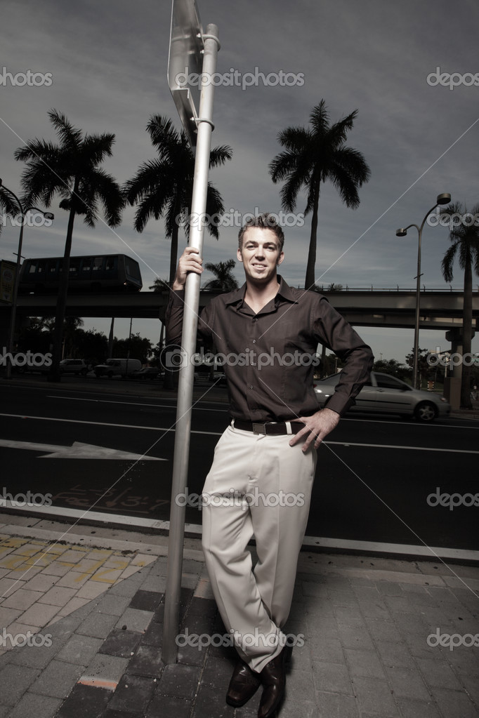 Handsome man leaning on a metal pole — Stock Photo #2586737