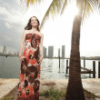 Fashionable woman by a palm tree — Stock Photo