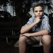 Foto Stock: Boy sitting in the dark