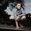 Foto Stock: Boy squatting on a table