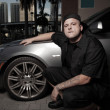 Young gangster posing by a sports car — Stock Photo