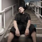 Young man sitting in an urban setting — Stock Photo