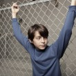 Boy posing by a fence — Stock Photo