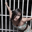 Stock Photo: Woman posing by a garage fence