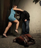 Woman beating up the criminal — Stock Photo