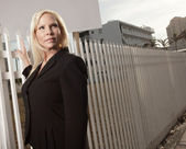 Businesswoman by the fence — Stock Photo