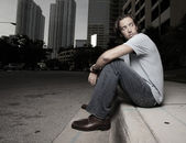 Man sitting on the curb — Stock Photo