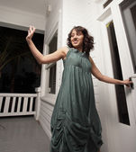 Woman waving and opening the door — Stock Photo