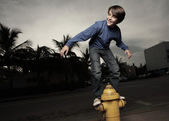 Boy on a fire hydrant — Stock Photo