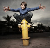 Young boy on a fire hydrant — Stock Photo
