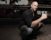 Człowiek w kucki z kciuki gest — Zdjęcie stockowe