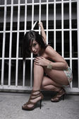 Woman squatting by the fence — Stock Photo