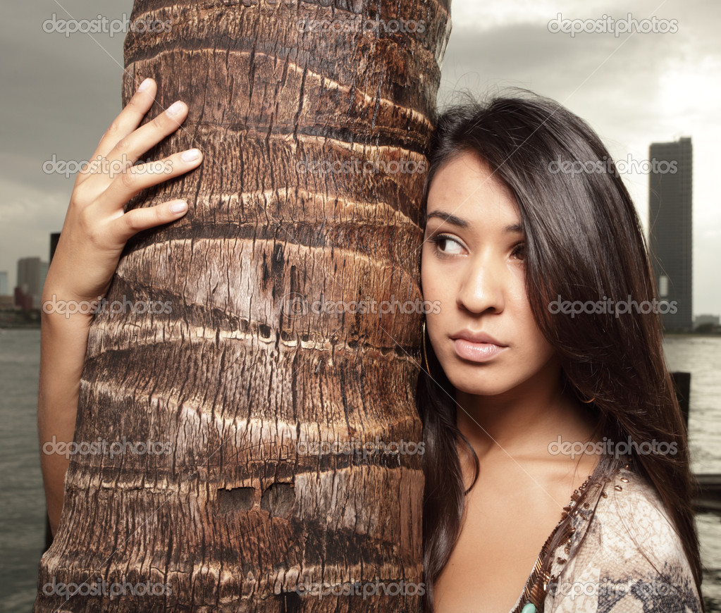 Beautiful woman with her arm wrapped around a tree  Stock Photo #2590883