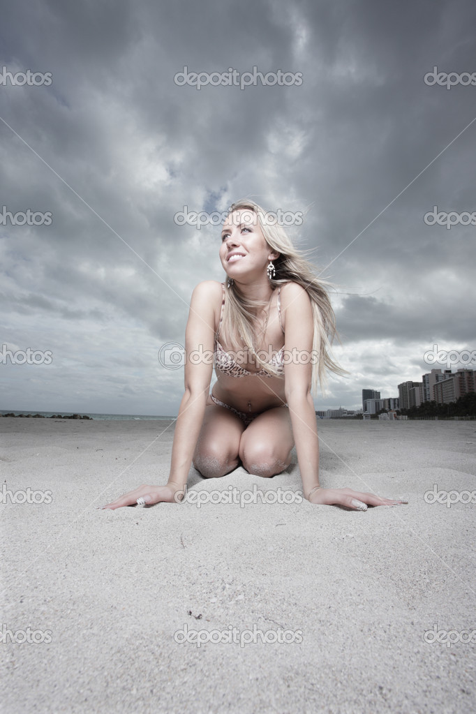 Woman in a bikini kneeling on the beach sand — Stock Photo #2595319