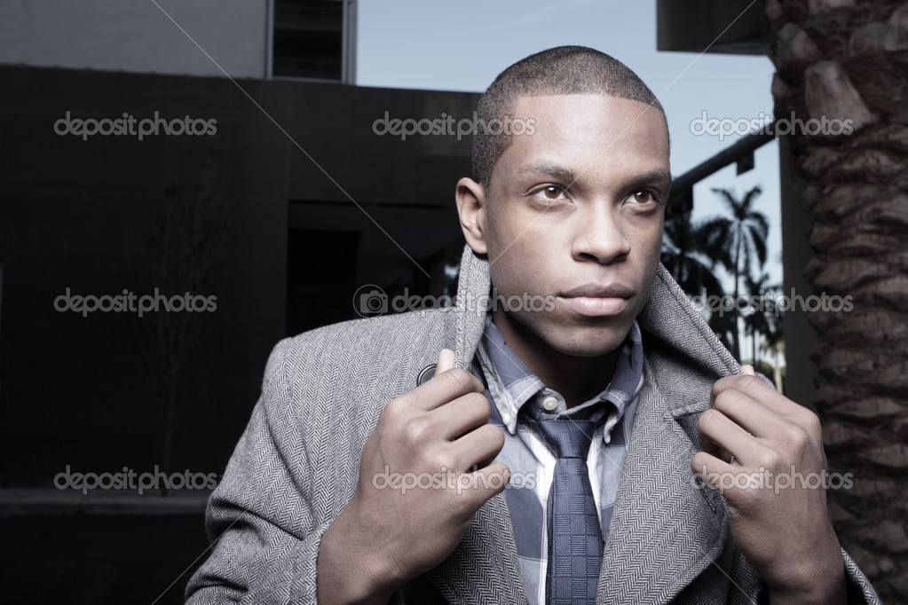 Handsome black man posing with his hands on his coat collar — Stock Photo #2597030