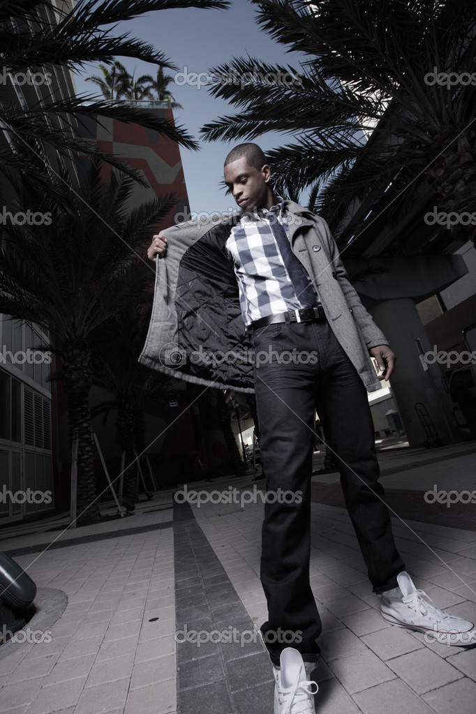 Young black man looking inside his jacket pocket — Stock fotografie #2597048