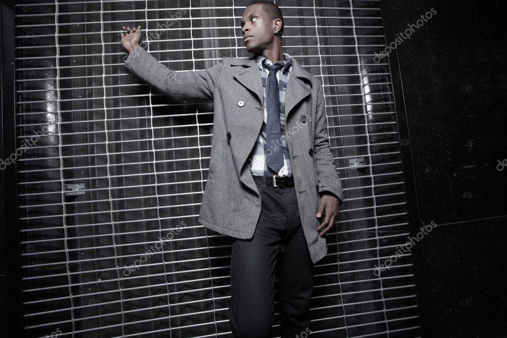 Young African American man posing by a security fence at night  — Photo #2597065