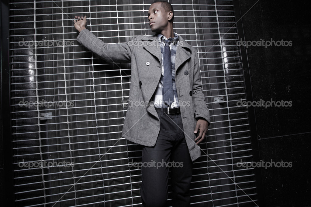 Young African American man posing by a security fence at night  — Stok fotoğraf #2597065