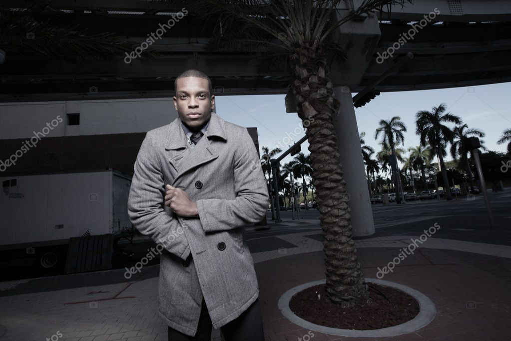 Young man in an urban setting wearing a wool coat to keep warm — Stockfoto #2597066