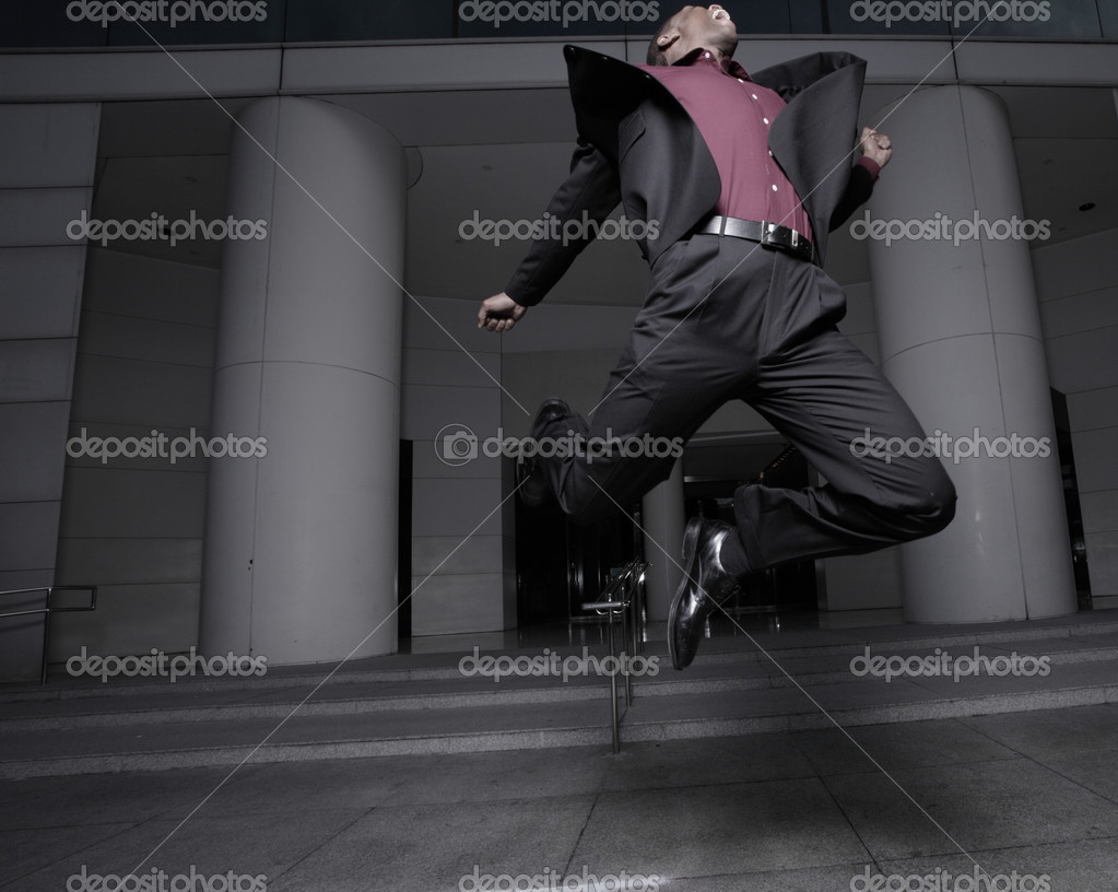 Young businessman jumping for joy after receiving a raise at work  Foto de Stock   #2597301