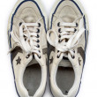 Old white worn sneakers seen from above — Stock Photo