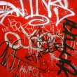 Graffiti on red, vertical — Stock Photo
