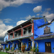 Chinese blue mansion under cloudy sky - Stock Photo