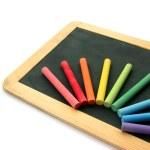 Blackboard and chalks in rainbow — Stock Photo