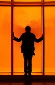 Silhouette in front of orange window — Stock Photo
