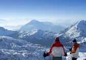 Two skiers looking over mountains top — Stock Photo