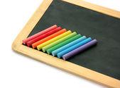 Blackboard and chalks in rainbow — Stockfoto