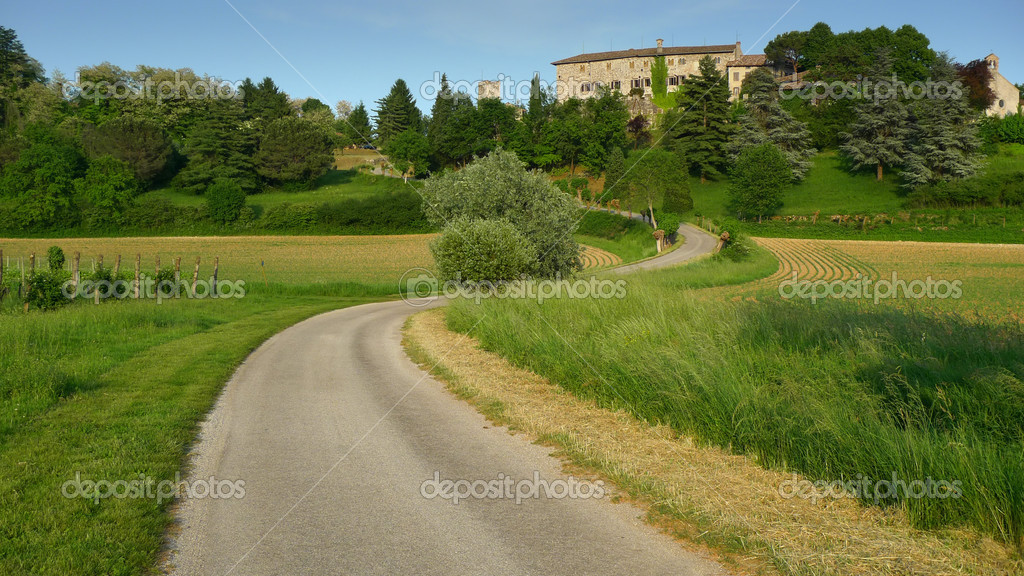 Bending road leading to Arcano castle near Udine, Italy. Sunset warm light. — Stock Photo #2480961