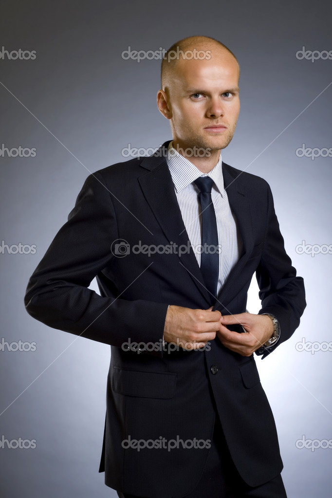 Picture of a young businessman buttoning his coat — Stock Photo #2333399
