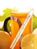 Thermometer with tea and lemon — Stock Photo