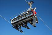 A single chair of a chairlift transporting skiers vivid blue sky — Stock Photo