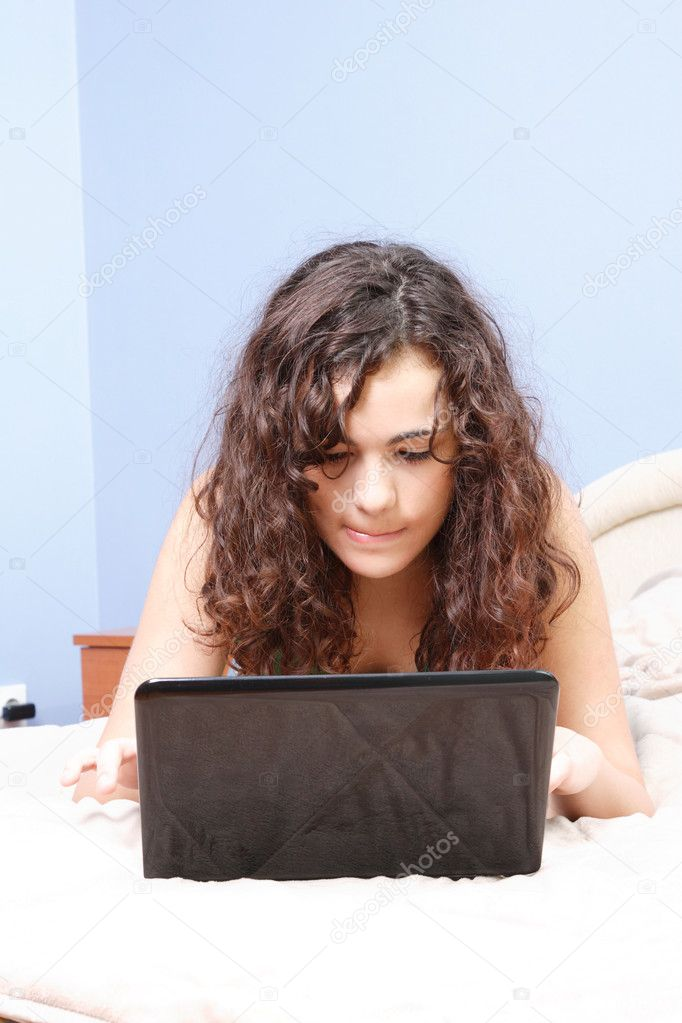 Teen girl in her bed looking on her laptop