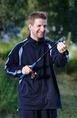 Young man smile with fishing rod — Stock Photo