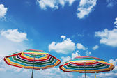 Two beach umbrella and blue cloudy sky — Stock Photo
