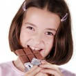 Young girl eats bar of chocolate — Stock Photo
