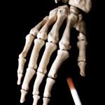 Skeleton hand drop a cigarette — Stock Photo