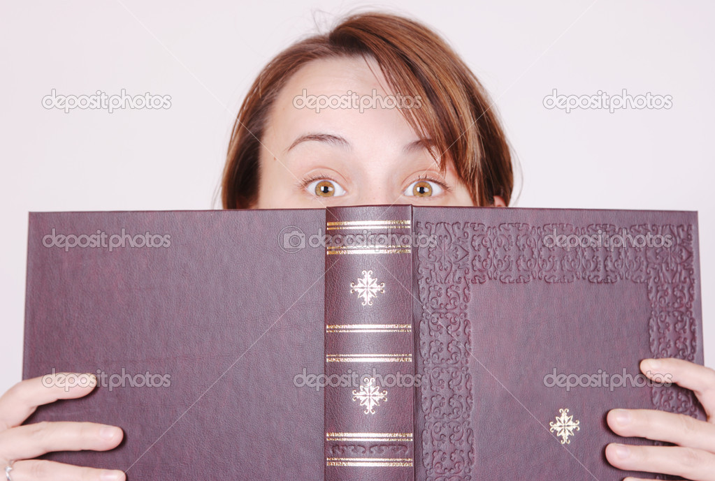 Young woman hiding behind the book, staring at you — Stock Photo #2380392