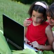Sisters with laptop outdoor — Stock Photo
