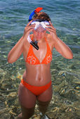 Young woman in orange bikini with diving goggles — Stock Photo