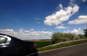 Road, car, blue cloudy sky — ストック写真